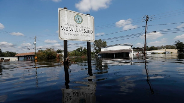 A sign commemorating the rebuilding of the town of Nichols, which was flooded two years earlier from Hurricane Matthew, stands in floodwaters in the aftermath of Hurricane Florence in Nichols, S.C., Friday, Sept. 21, 2018. Virtually the entire town is once again flooded and inaccessible except by boat.