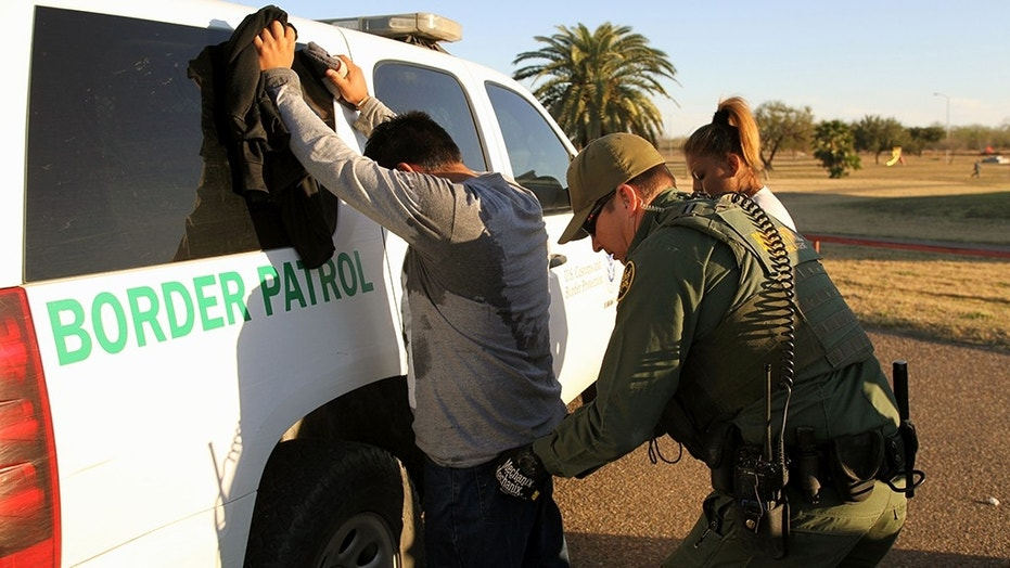 A Border Patrol agent takes a man into custody for allegedly entering the U.S. illegally by crossing the Rio Grande River in south Texas, Feb. 9, 2016.