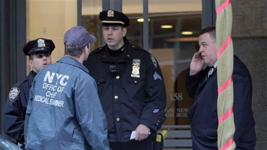 A member of the NYC Office of Chief Medical Examiner speaks to officers of the New York Police Department in front of the apartment where Mark Madoff lived in New York. Madoff, the son of disgraced financier Bernard Madoff, was found dead Saturday, Dec. 11, 2010 of an apparent suicide, according to a law enforcement official. Madoff, 46, was found hanged in his apartment in Manhattan's SoHo section, according to the official. A family member notified police around 7:30 a.m. (AP Photo/Mary Altaffer)