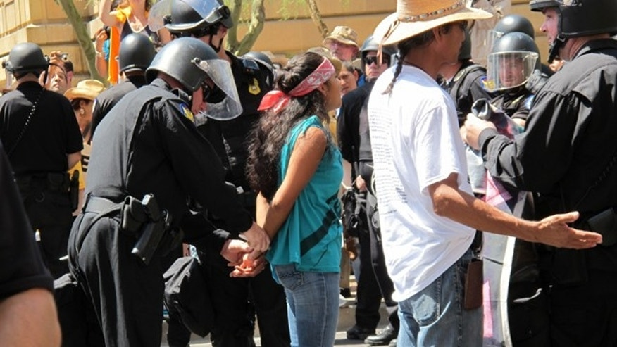 Protesters of Arizona's new Immigration law are arrested by police wearing riot gear during the protest in Phoenix, AZ.