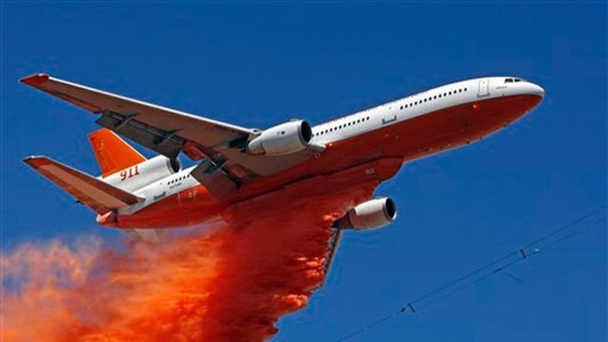 A DC-10 jumbo jet tanker carrying 12,000-gallon loads drops swaths of fire retardant on top of the crest of Hauser Peak to protect microwave towers in Palmdale, Calif, on Friday, July 30, 2010. (AP Photo/Damian Dovarganes)