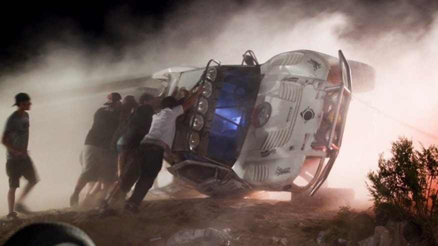 Workers push an overturned off-road race truck upright Sunday after it went out of control and plowed into a crowd of spectators during a race earlier in Lucerne Valley, Calif., Saturday, Aug. 14, 2010. At least eight people were killed during the incident about 100 miles east of Los Angeles.(AP Photo/Francis Specker)