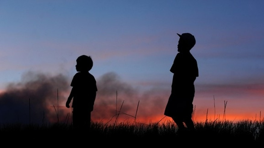 Campbell Kujawa-Black, 6, and Dawson Cross, 8, right, watch a fire burn at sunset, Sunday, Sept. 12, 2010, near the Bison Visitor Center west of Loveland, Colo. (AP Photo/The Coloradoan, Dawn Madura)