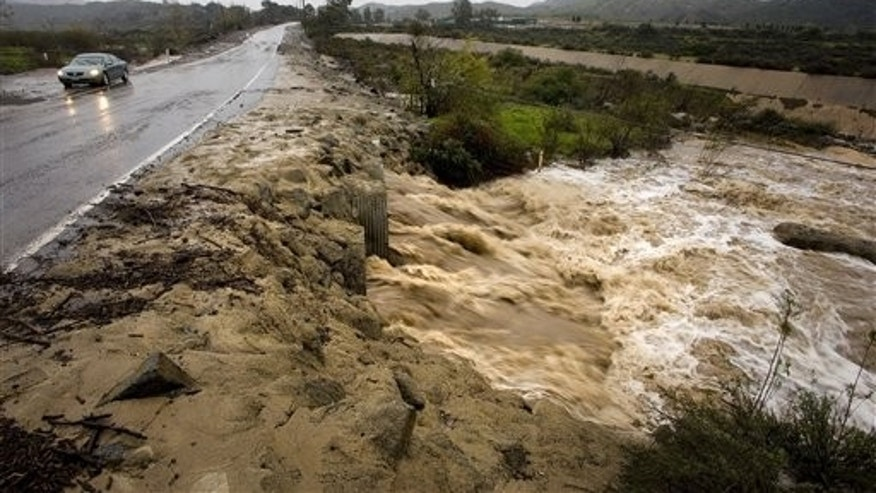 A rain-swollen Silverado Creek runs beneath Black Star Canyon Road early Tuesday, Dec. 21, 2010 in Silverado Canyon, Calif. The latest in a series of powerful storm systems is bearing down on California, pelting mountain areas with heavy rain, snow and high winds, prompting evacuations and leaving thousands without power. (AP Photo/Orange County Register, Mark Rightmire)  NO SALES; MAGS OUT; LOS ANGELES TIMES OUT.