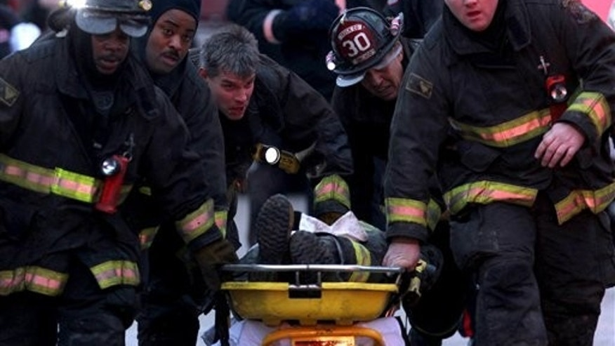 Chicago firefighters evacuate an injured firefighter from an abandoned commercial building in the city's South Side where the building's roof collapsed during a blaze Wednesday, Dec. 22, 2010. (AP Photo/Chicago Tribune, E. Jason Wambsgans) NO SALES