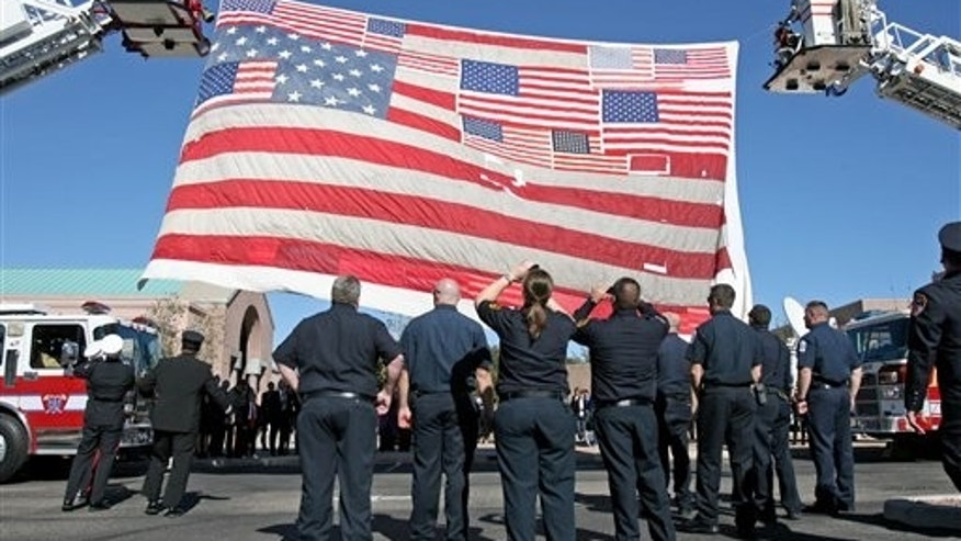 Firefighters raise the large American flag recovered from Ground Zero after the 9/11 attacks outside the entrance at the St. Elizabeth Ann Seton Church for the funeral of 9-year-old Christina Taylor Green Thursday, Jan. 13, 2011, in Tucson, Ariz. Green, the youngest victim of Saturday's shooting in Tucson, was born on the day of the Sept. 11 attacks in 2001.  (AP Photo/Mamta Popat, Pool)