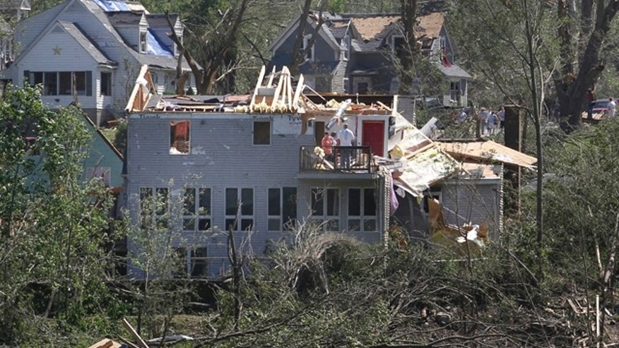People stand on a deck of their damaged home in Monson, Mass. Thursday, June 2, 2011 one day after it was devastated by a tornado.   Residents of 19 communities in central and western Massachusetts woke to widespread damage Thursday, a day after at least two late-afternoon tornadoes shocked emergency officials with their suddenness and violence and caused the state's first tornado-related deaths in 16 years.  (AP Photo/Elise Amendola)