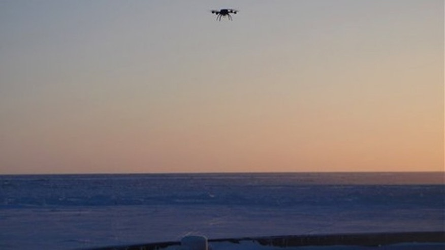 In this Tuesday, Jan. 10, 2012 photo provided by the University of Alaska in Fairbanks, an Aeryon Scout unmanned aerial vehicle hovers at the Nome causeway in Nome, Alaska. Researchers were using the 2.5-pound camera-equipped drone to provide a large picture of the ice in hopes of guiding a Nome-bound Russian fuel tanker as close to shore as possible. The drone glides on 20-minute missions ranging from 10 feet to 320 feet above the ice, and its images can be instantly viewed on a tablet-type computer screen. (AP Photo/University of Alaska Geophysical Institute, David Giessel)