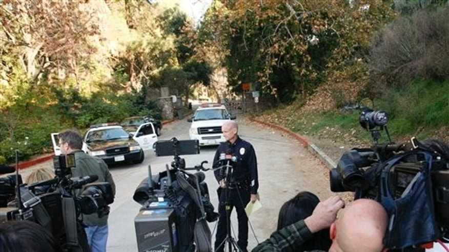 Los Angeles Police Commander Andrew J. Smith, center, prepares to speak to media in front of the Bronson Canyon Park entrance as Los Angeles Police detectives search the neighborhood below the Hollywood Sign after a plastic bag containing a human head was discovered Tuesday on a nearby trail in Los Angeles, Wednesday, Jan. 18, 2012. (AP Photo/Jason Redmond)