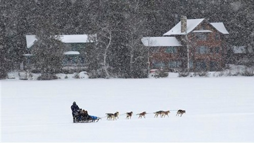 A dogsled team pulls passengers on a snowy Adirondack morning ride on Mirror Lake in Lake Placid, N.Y., on Saturday, Jan. 21, 2012. (AP Photo/Mike Groll)