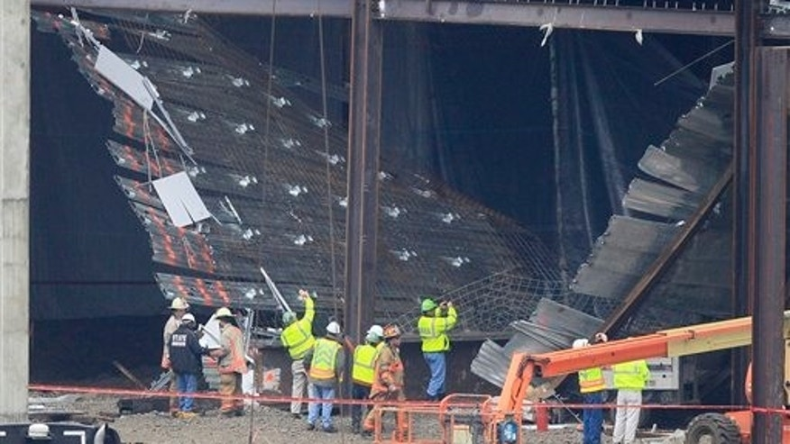 Workers and officials inspect the scene of a collapse at the Horseshoe Casino under construction, Friday, Jan. 27, 2012, in Cincinnati. Authorities in Cincinnati say at least 11 people have been taken to hospitals with minor injuries, non life-threatening. (AP Photo/Al Behrman)