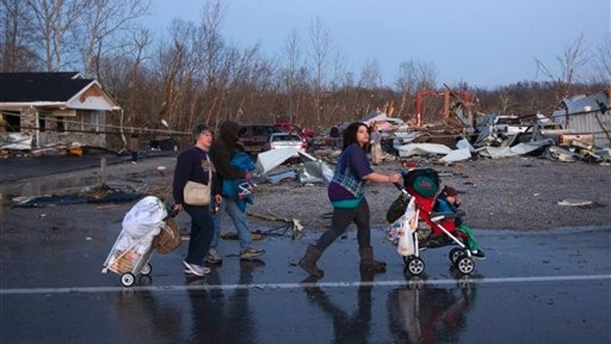 A family walks by damaged buildings that lay in ruin after a tornado touched near Henryville, Ind., Friday March 2, 2012.  The storm was part of a system that brought high winds and heavy rain to parts of Indiana, Kentucky and Tennessee.  (AP Photo/Philip Scott Andrews)