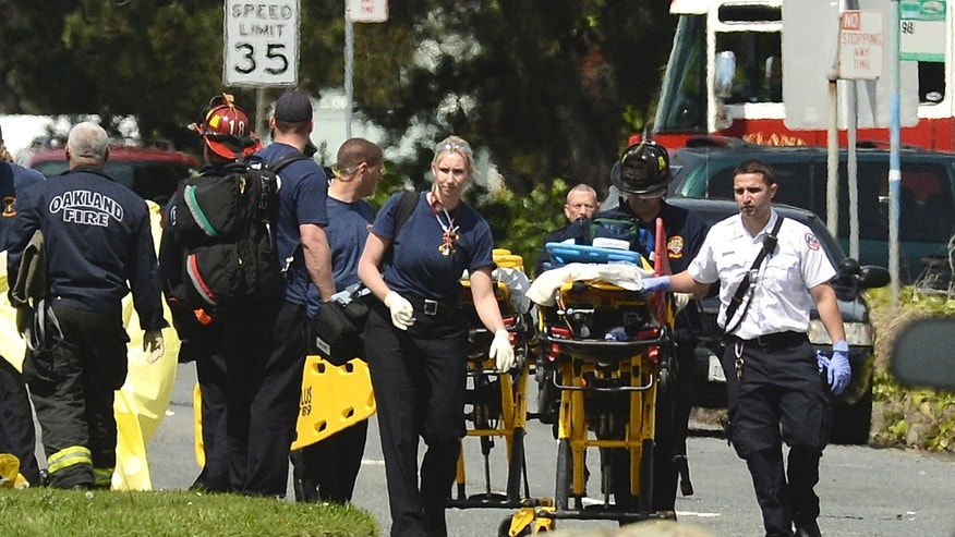 Emergency officials walk with a gurney outside of Oikos University in Oakland, Calif., Monday, April 2, 2012. A suspect was detained Monday in a shooting attack at a California Christian university that sources said has left at least five people dead. (AP Photo/Noah Berger)