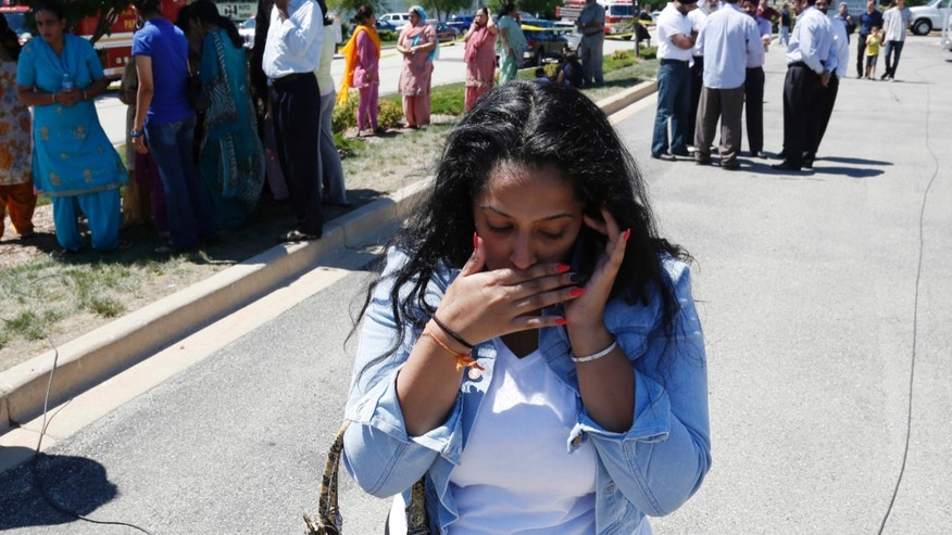 A woman reacts with others as they await word on a shooting at a Sikh temple in Oak Creek, Wis., Sunday, Aug. 5, 2012, where police and witnesses describe a chaotic situation with an unknown number of victims, suspects and possible hostages. (AP Photo/Jeffrey Phelps)