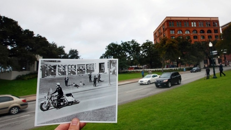 This Nov. 5, 2013 photo shows an image taken by Dallas Morning News photographer Tom Dillard on Nov. 22, 1963, of spectators lying on the ground in Dealey Plaza as a motorcycle police officer drives by immediately after the shooting of U.S. President John F. Kennedy, juxtaposed outside of the current day Elm Street, in Dallas. (AP Photo/Houston Chronicle, Cody Duty)