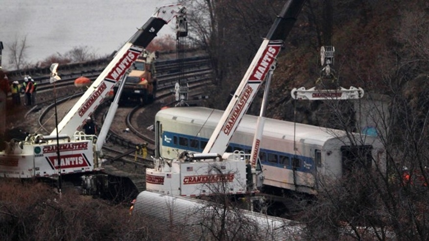 "Cranes lift a derailed Metro-North train car, Monday, Dec. 2, 2013, in the Bronx borough of New York. Federal authorities began righting the cars Monday morning as they started an exhaustive investigation into what caused a New York City commuter train rounding a riverside curve to derail, killing four people and injuring more than 60 others. A second ""event recorder"" retrieved from the train may provide information on the speed of the train, how the brakes were applied, and the throttle setting, a member of the National Transportation Safety Board said Monday.  (AP Photo/Mark Lennihan)"