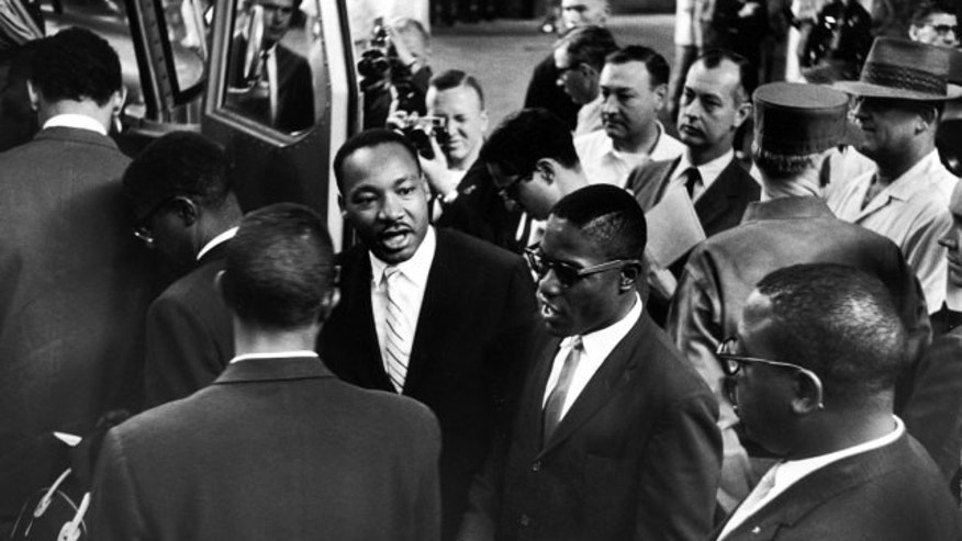 Martin Luther King Jr. encourages freedom riders as they board a bus for Jackson, Miss., 1961.