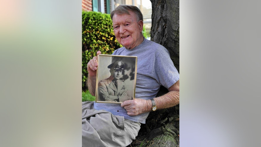 Mike Smith holds an old photograph of his brother, Army Col. Gene Smith, outside his Wilmington home last summer after the rediscovery of the wreckage of the Air Force plane his brother was killed aboard when it crashed in Alaska in 1952.  News Journal file