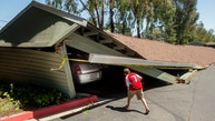 A boy examines cars trapped beneath a collapsed carport at Charter Oaks apartments in Napa, Calif., following an earthquake Sunday, Aug. 24, 2014. More than fifteen vehicles were trapped or crushed as multiple carports collapsed at the complex during a large earthquake. (AP Photo/Noah Berger)