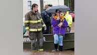 """Bossier City Firemen and volunteers help Elaine Christy and her dog """"Boo"""" as they evacuate from rising water at the Pecan Valley Estates trailer park in Bossier City, La., Wednesday, March 9, 2016. (AP Photo/Gerald Herbert)"""