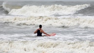 A surfer makes his way out into increasingly rough Atlantic Ocean waters before the arrival of Hurricane Matthew, in Isle of Palms, South Carolina, U.S., October 7, 2016. REUTERS/Jonathan Drake - RTSRA2W