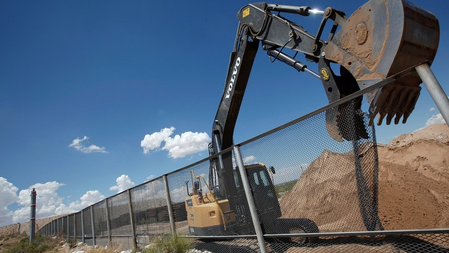 An excavator removes a fence, which will be replace by a section of the U.S.-Mexico border wall at Sunland Park, U.S. opposite the Mexican border city of Ciudad Juarez, Mexico, August 26, 2016. Picture taken from the Mexico side of the U.S.-Mexico border. REUTERS/Jose Luis Gonzalez - RTX2N898