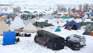 People walk through the Dakota Access Pipeline protest camp on the edge of the Standing Rock Sioux Reservation near Cannon Ball, North Dakota, U.S., January 24, 2017. REUTERS/Terray Sylvester - RTSX754