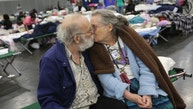 Don and Peg Sauter kiss as they take refuge from Tropical Storm Harvey at the George R. Brown Convention Center in Houston on Tuesday, Aug. 29, 2017 in Houston.  The couple celebrated their 55th wedding anniversary on August 22 and moved from their assisted living home.   (Elizabeth Conley/Houston Chronicle via AP)