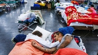 Tammy Dominguez, left, and her husband, Christopher Dominguez, sleep on cots at the George R. Brown Convention Center where nearly 10,000 people are taking shelter after Tropical Storm Harvey, Wednesday, Aug. 30, 2017, in Houston. They have been at the shelter since evacuating Houston's Northside on Sunday. (Michael Ciaglo/Houston Chronicle via AP)