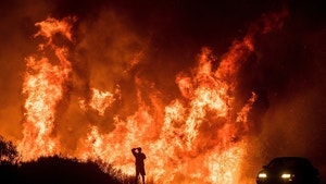 A motorists on Highway 101 watches flames from the Thomas fire leap above the roadway north of Ventura, Calif., on Wednesday, Dec. 6, 2017.  As many as five fires have closed highways, schools and museums, shut down production of TV series and cast a hazardous haze over the region. About 200,000 people were under evacuation orders. No deaths and only a few injuries were reported. (AP Photo/Noah Berger)