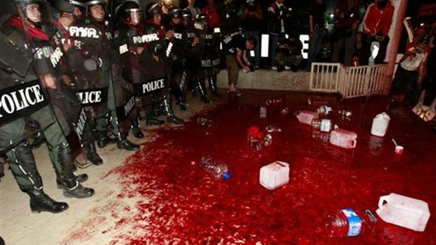 March 16: Thai police officers stand next to sea of blood after protesters and supporters of ousted Prime Minister Thaksin Shinawatra poured it on the ground at the ruling Democrat Party building.
