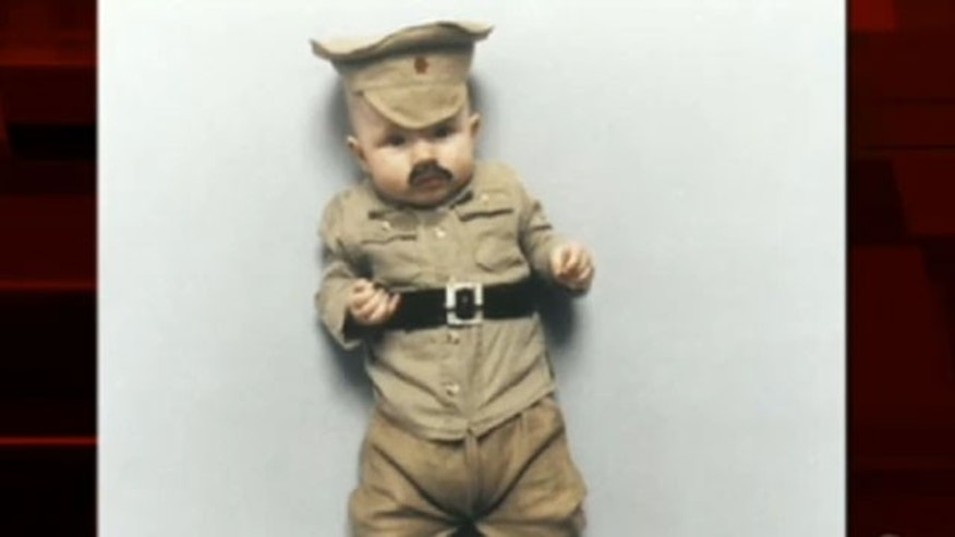 Danish artist's baby is dressed as different world dictators for exhibit.