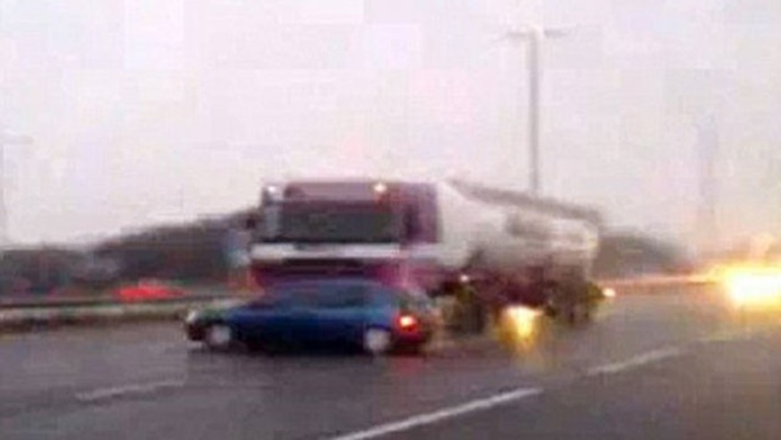 Truck driver appears unaware he is pushing a  Renault down a British highway at 60 mph.