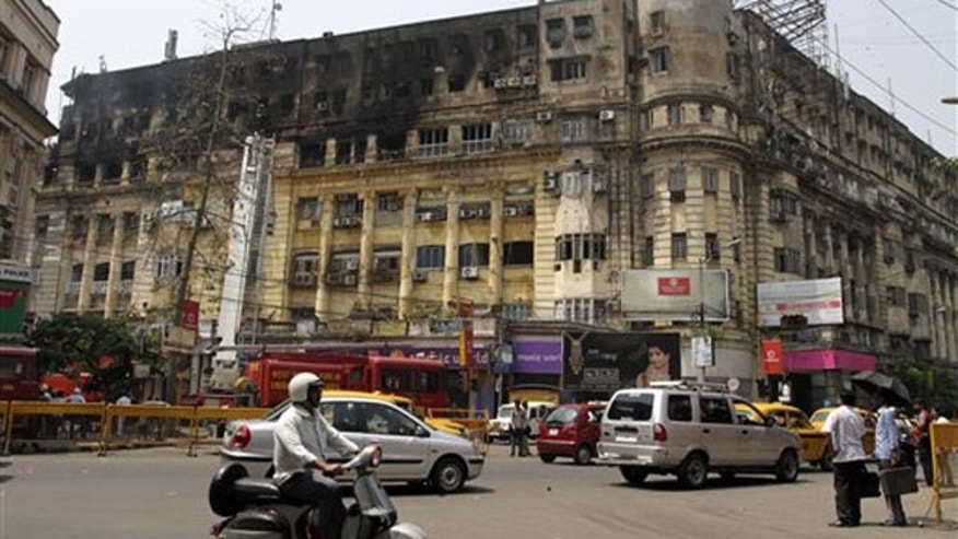 March 24: Commuters move past a seven-story building that caught fire in Calcutta, India.