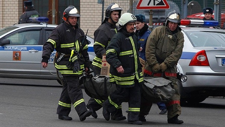 Mar. 29: Emergency Ministry officers and firefighters carry a body from Lubyanka metro station in downtown Moscow.