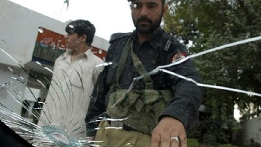 File: Pakistani police officer looks at a shattered windshield of the car of Iranian diplomat, Heshmatollah Attarzadeh, after he was kidnapped in Peshawar, Pakistan.
