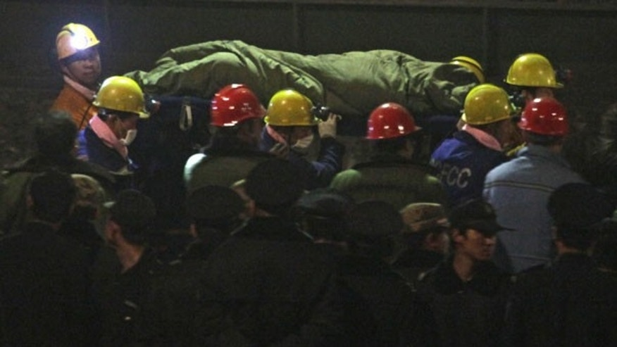 April 5: Rescue workers carry a survivor on a stretcher to a waiting ambulance at the Wangjialing Coal Mine in Xiangning county in north China's Shanxi province. (AP)