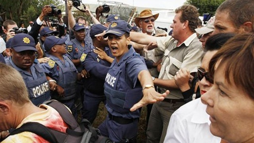 April 6: Followers of slain white supremacist leader Eugene Terreblanche scuffle with police outside the courthouse in Ventersdrop, South Africa.
