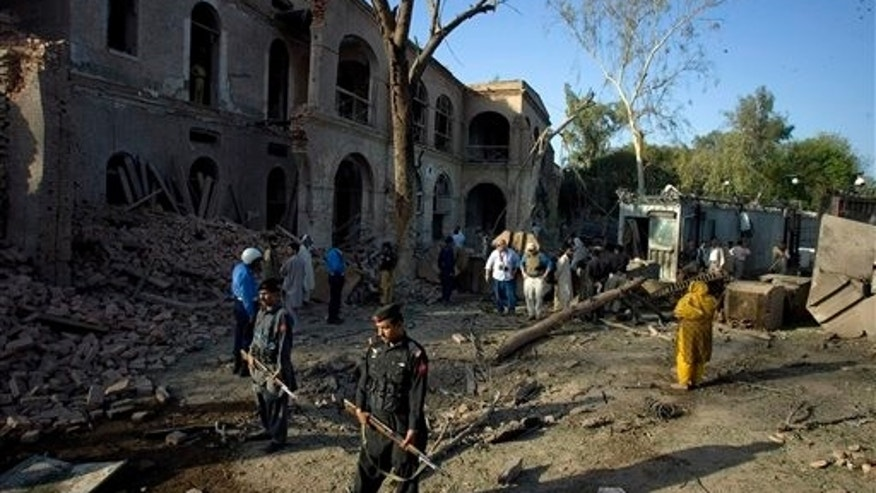 April 5: Unidentified U.S. security officials, center, examine the site of suicide bombing near the U. S. Consulate in Peshawar, Pakistan. Islamist militants attacked a U.S. consulate in northwest Pakistan with car bombs and grenades Monday, killing three people, hours after 41 people died in a suicide attack on a political rally elsewhere in the region.