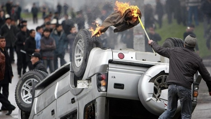 April 7: A demonstrator sets fire on a car during clashes between riot police and anti-government protesters near the presidential administration in Bishkek.