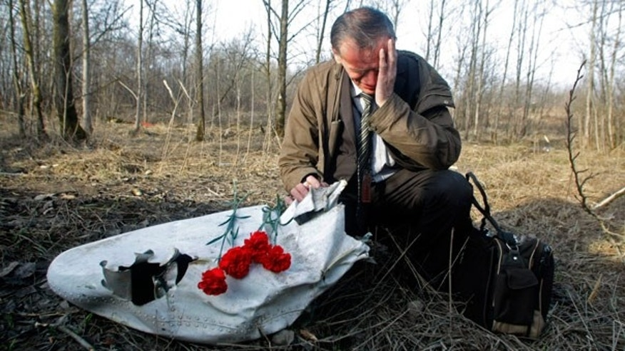 April 11: Ian Grushinski grieves by a piece of the wreckage at the plane crash site near Smolensk, Russia.