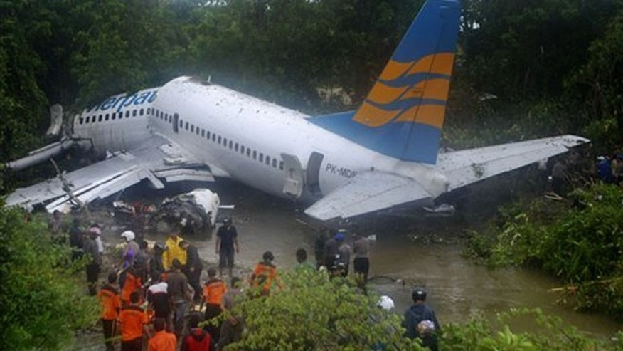 April 13: Rescuers gather near the wreckage of a Boeing 737 operated by Merpati Nusantara Airlines after it skidded off the runway at Rendani airport in Manokwari, Papua province, Indonesia.