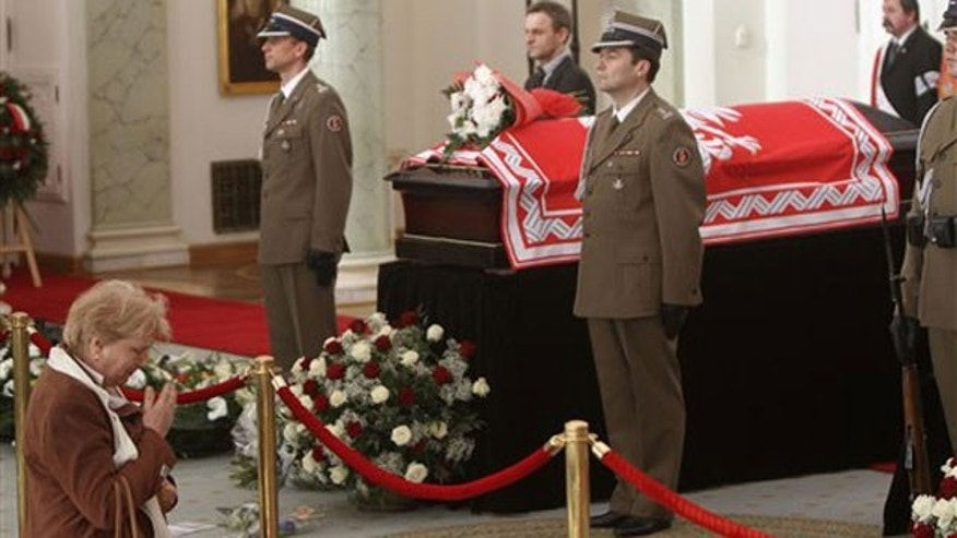 April 13: A woman prays in front of the coffins of late Polish Presidential couple lying in state in Warsaw, Poland.