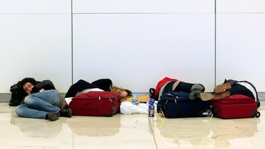 April 18: Stranded air travelers rest as they wait for flights at Barajas Airport, in Madrid, Spain.