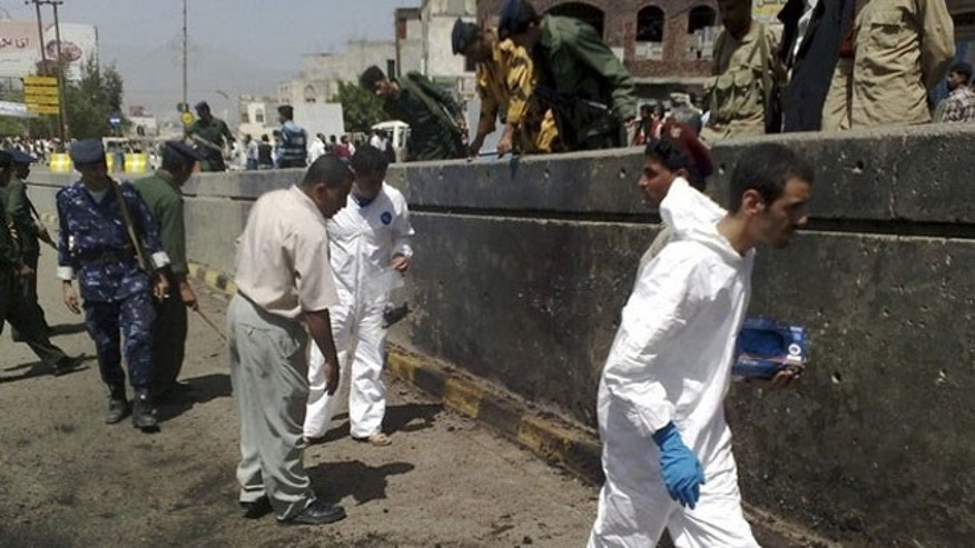 Police and forensic officers gather evidence from the site of a suicide bomb blast in Sanaa April 26, 2010. An explosion near the convoy of the British ambassador to Yemen on Monday killed one person, believed to be a suicide bomber, but the envoy was unharmed, a security source and British officials said (Reuters).