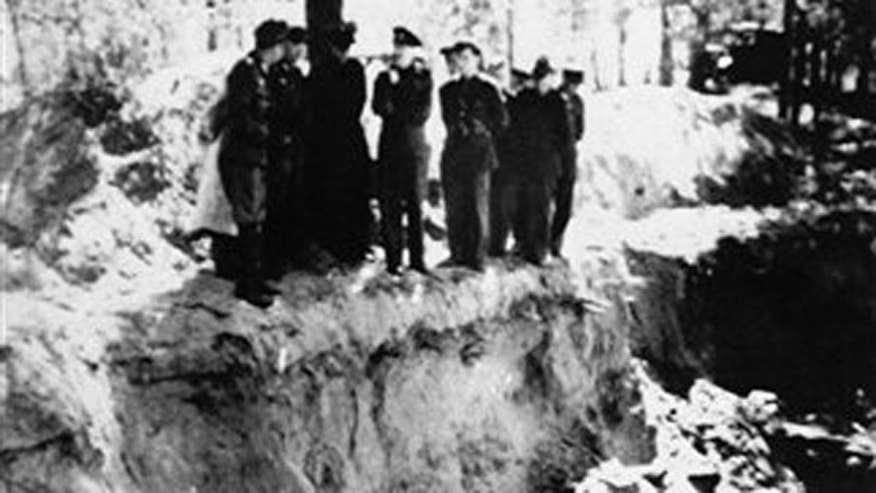 In this May 1943 file photo, two German officers, left, and a group of Allied officers who were prisoners of war look over a partly-emptied mass grave in the Katyn Forest in Russia. Russia's state archives posted documents Wednesday April 28, 2010 for the first time on the Internet about the Soviet Union's World War II massacre of more than 20,000 Polish officers and other prominent citizens.