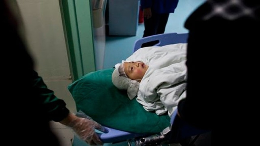 April 29: A child who was attacked at the Zhongxin Kindergarten is transferred into a hospital ward in east China's Jiangsu Province.