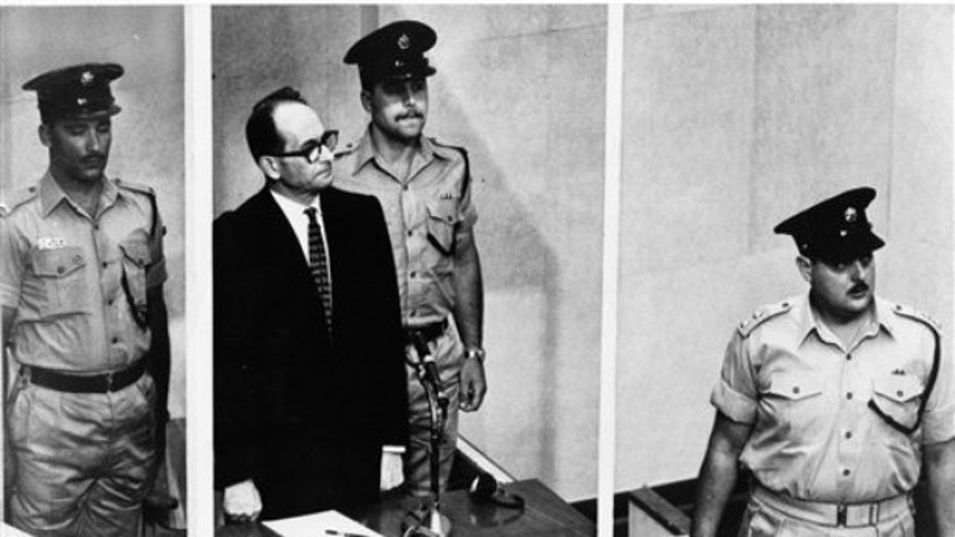 "1962: Adolf Eichmann stands in his glass cage, flanked by guards, in the Jerusalem courtroom where he was tried for war crimes committed during World War II. The basics of Adolf Eichmann's story are well-documented. He was commonly known as the ""architect of the Holocaust"" for his role in coordinating the Nazis' policy of genocide. He fled Germany only to be captured in Argentina by the Mossad, taken to Israel for trial, and hanged."