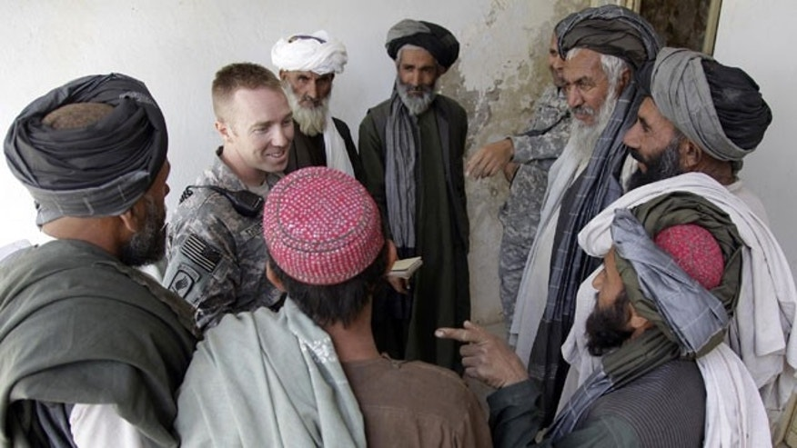 "In this Wednesday, April 28, 2010 photo, U.S. Army Capt. Casey Thoreen, second from left, of Seattle, Wash., Bravo Company, 2nd Battalion, 1st Infantry Regiment, 5th Stryker Brigade, talks with village leaders before the start of a shura , in the Maiwand district of Afghanistan's Kandahar province. To the locals, he is the ""King of Maiwand"" district testimony to the fact that without the resources the young captain and others like him provide, local government in much of insurgency-ravaged southern Afghanistan could not function at all."