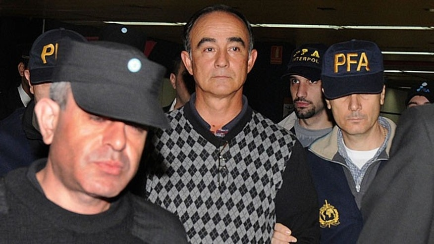 May 6: Police officers escort Argentine airline pilot Julio Alberto Poch upon his arrival at Buenos Aires airport after being extradited from Spain. (AP)